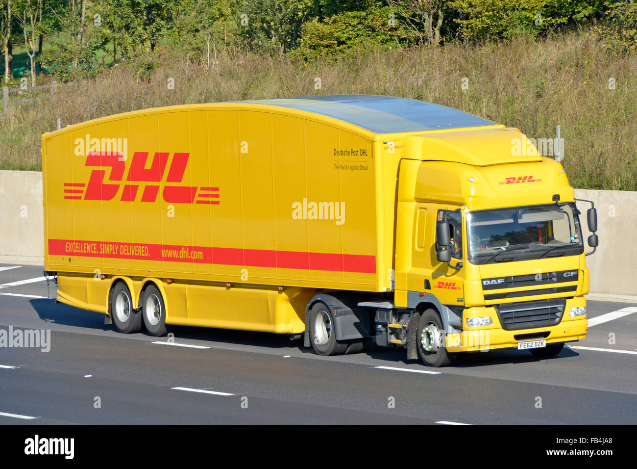 Deutsche Post DHL lorry and trailer driving along motorway shaped bodywork to reduce drag and to improve air flow - Stock Image