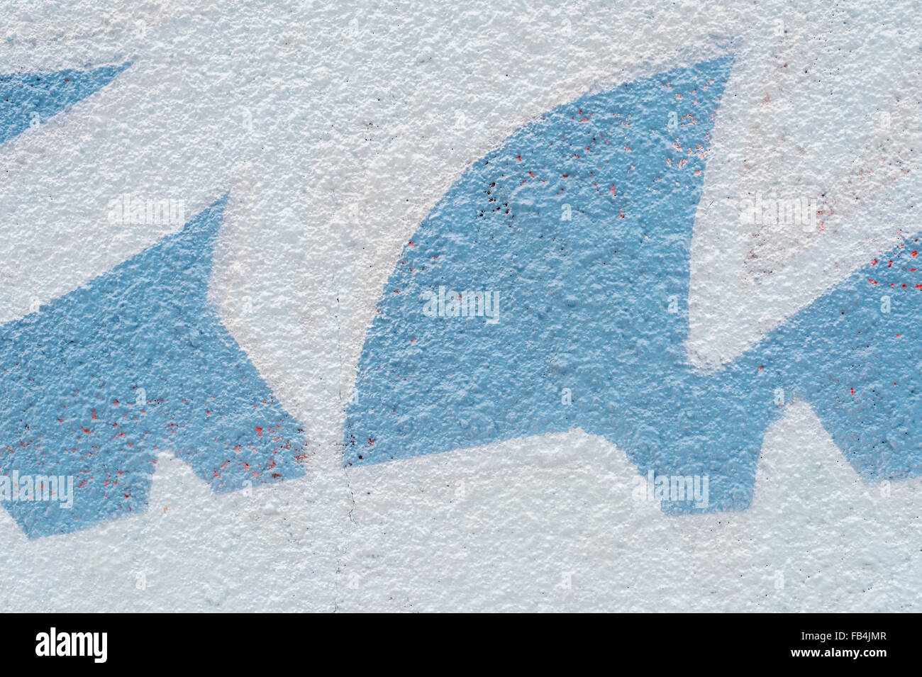 White cement wall with geometrical blue forms - Stock Image