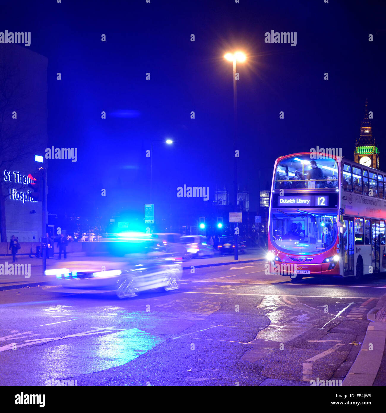Metropolitan police car with blue flashing lights illuminating night sky on Westminster Bridge with london bus waiting Stock Photo