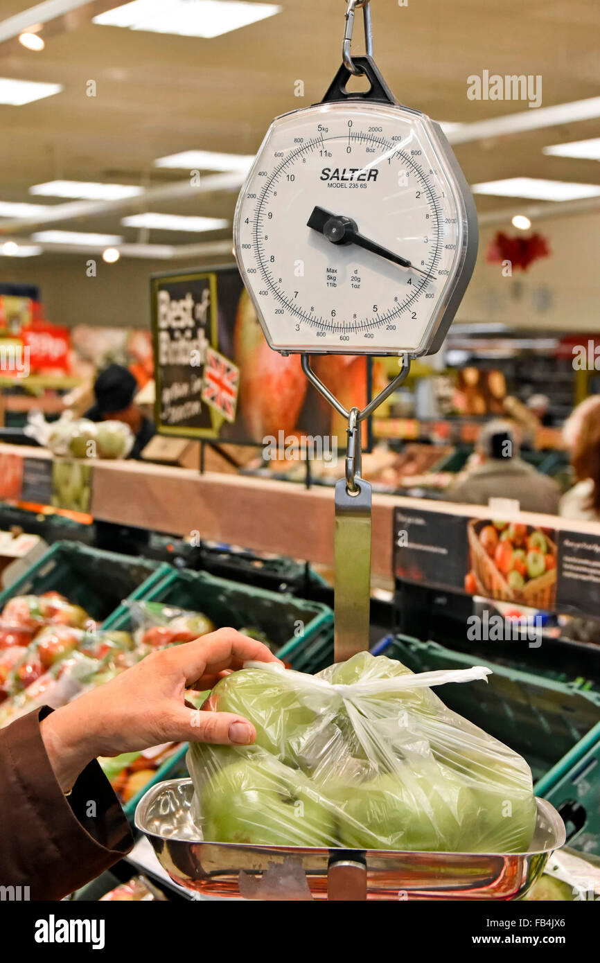 Salter weighing scales being used by a customer in a  fruit and vegetable department of a Tesco supermarket to weigh - Stock Image