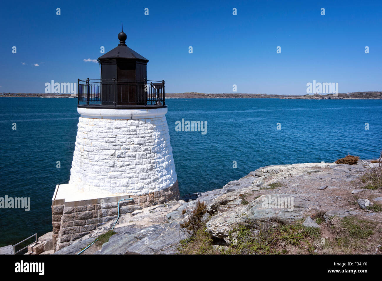 Stone tower of Castle Hill lighthouse, built on a rocky cliff, overlooking Narragansett Bay on a summer day in Newport, - Stock Image