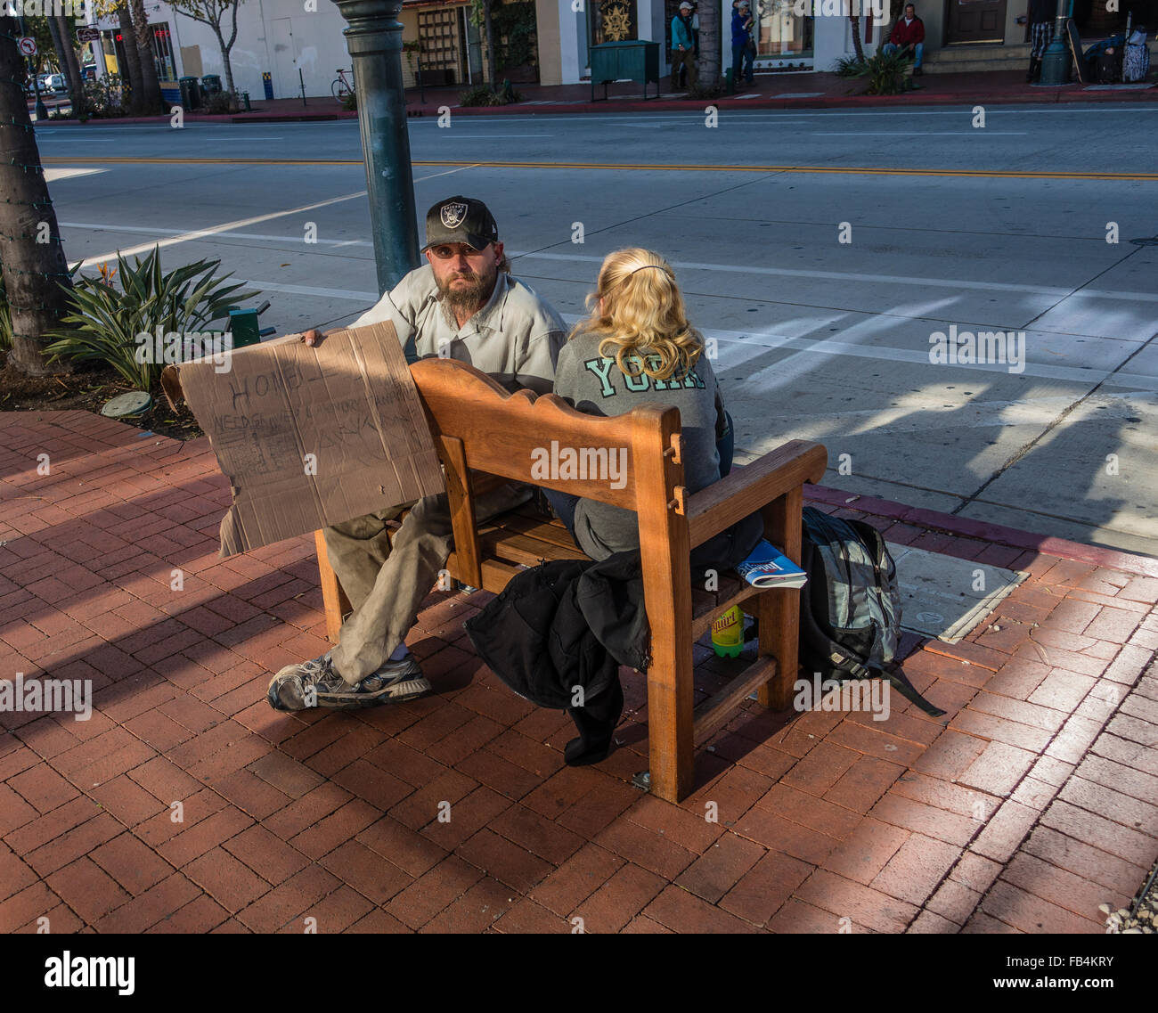 A homeless married couple begs while sitting on a bench on State Street in Santa Barbara, California. - Stock Image
