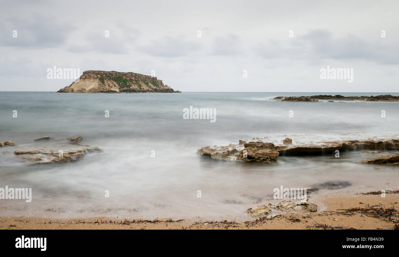 Rocky Seascape with the  small  island of geronisos st.  georges cape at  Paphos city in Cyprus - Stock Image