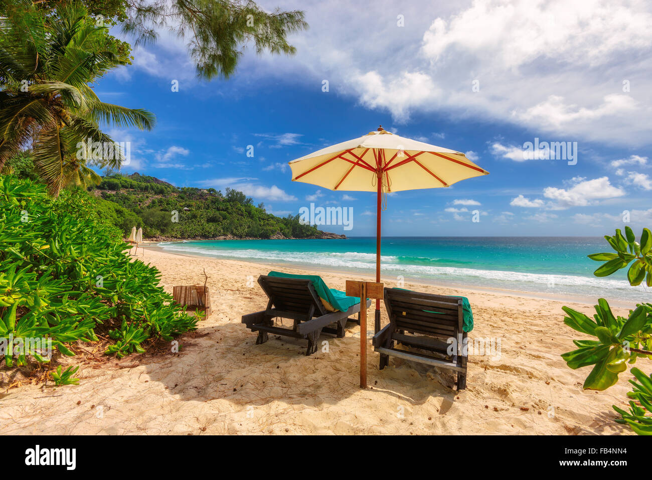 View of nice tropical empty sandy beach with umbrella and beach chair, Mahe Island, Seychelles - Stock Image