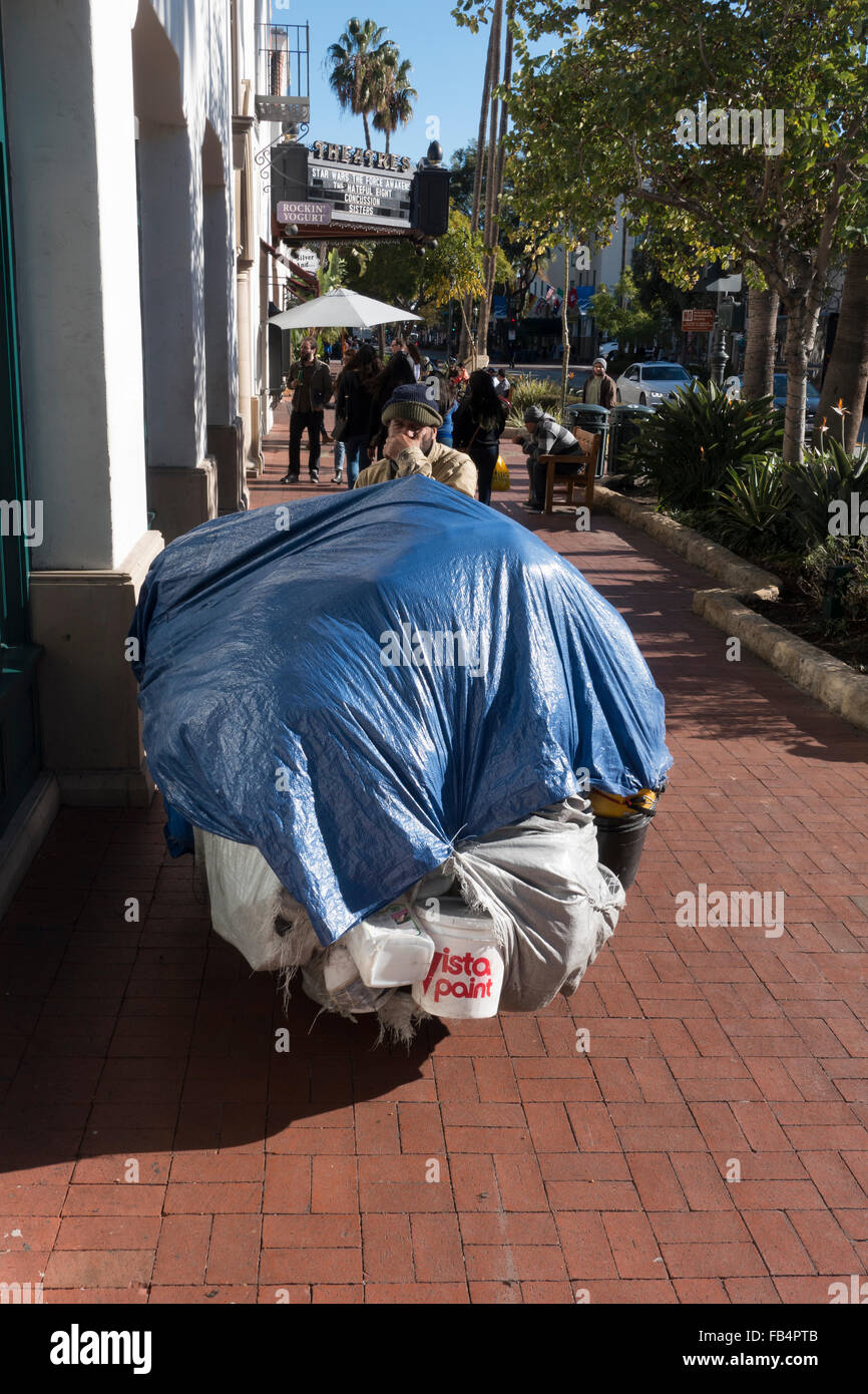A frontal view of a homeless man wearing a wool cap & tan coat standing behind his overloaded cart covered by - Stock Image