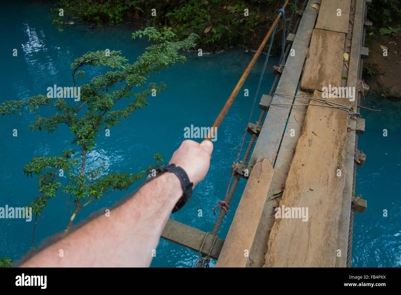 A tourist walks over a rickety bridge that crosses the milky blue water of the Rio Celeste, Costa Rica Stock Photo
