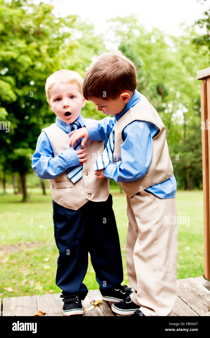 brothers in suits fixing tie - Stock Image