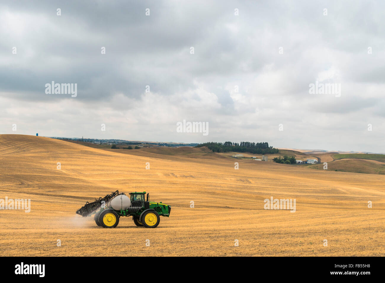 John Deere self propelled sprayer spraying herbicide on a field in advance of preparing it to plant in the Palouse - Stock Image