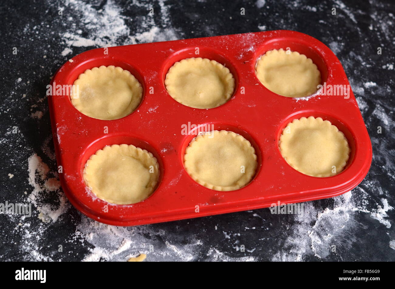 Red silicone muffin tray with unbaked mince pies on a dark floured surface - Stock Image
