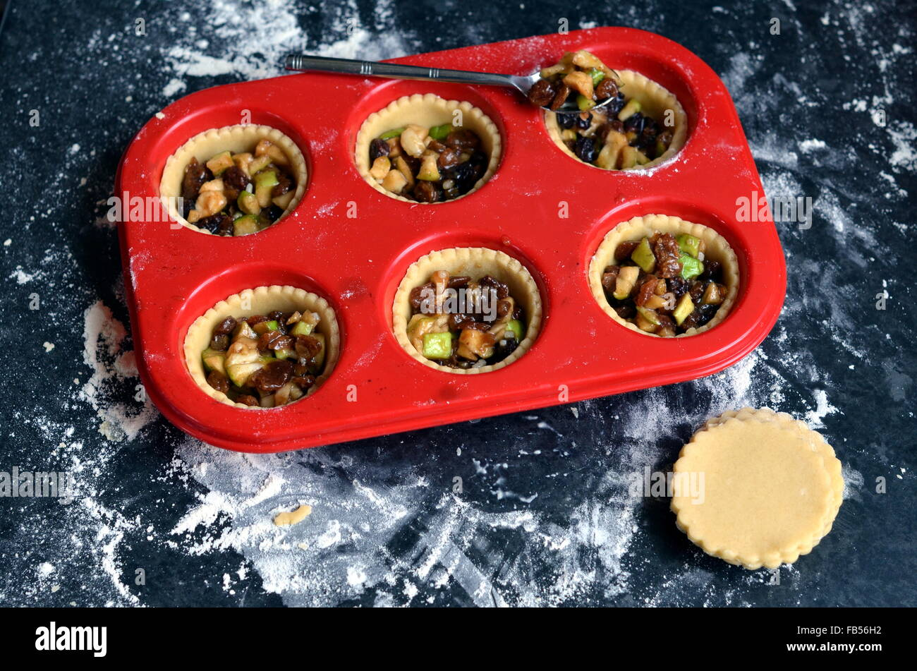 Red silicone muffin tray with unbaked open apple and mince pies on a dark floured surface - Stock Image