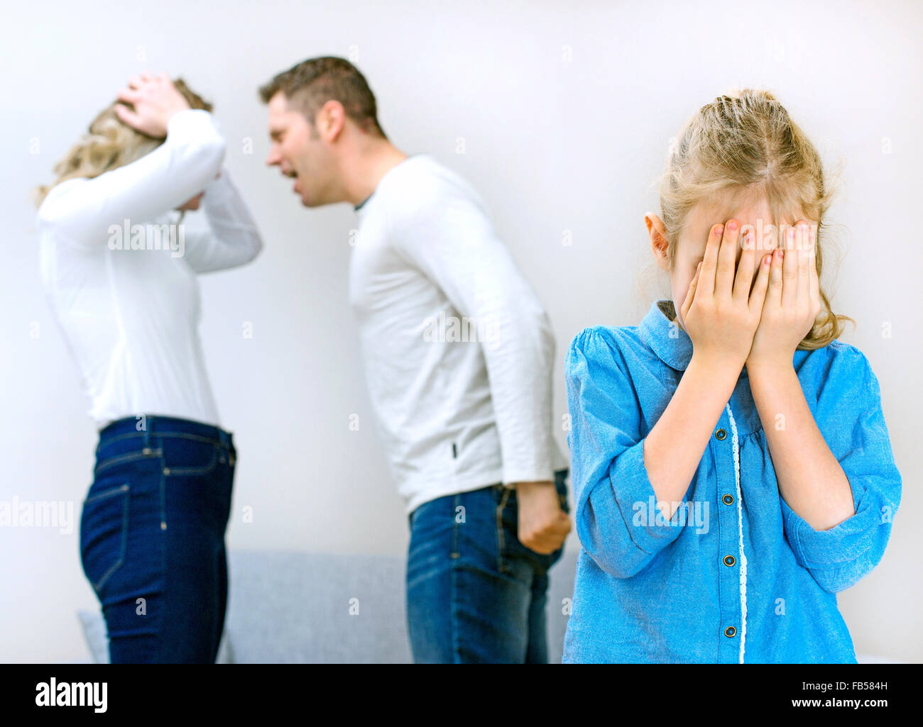 Parents quarreling at home, child in shock. - Stock Image
