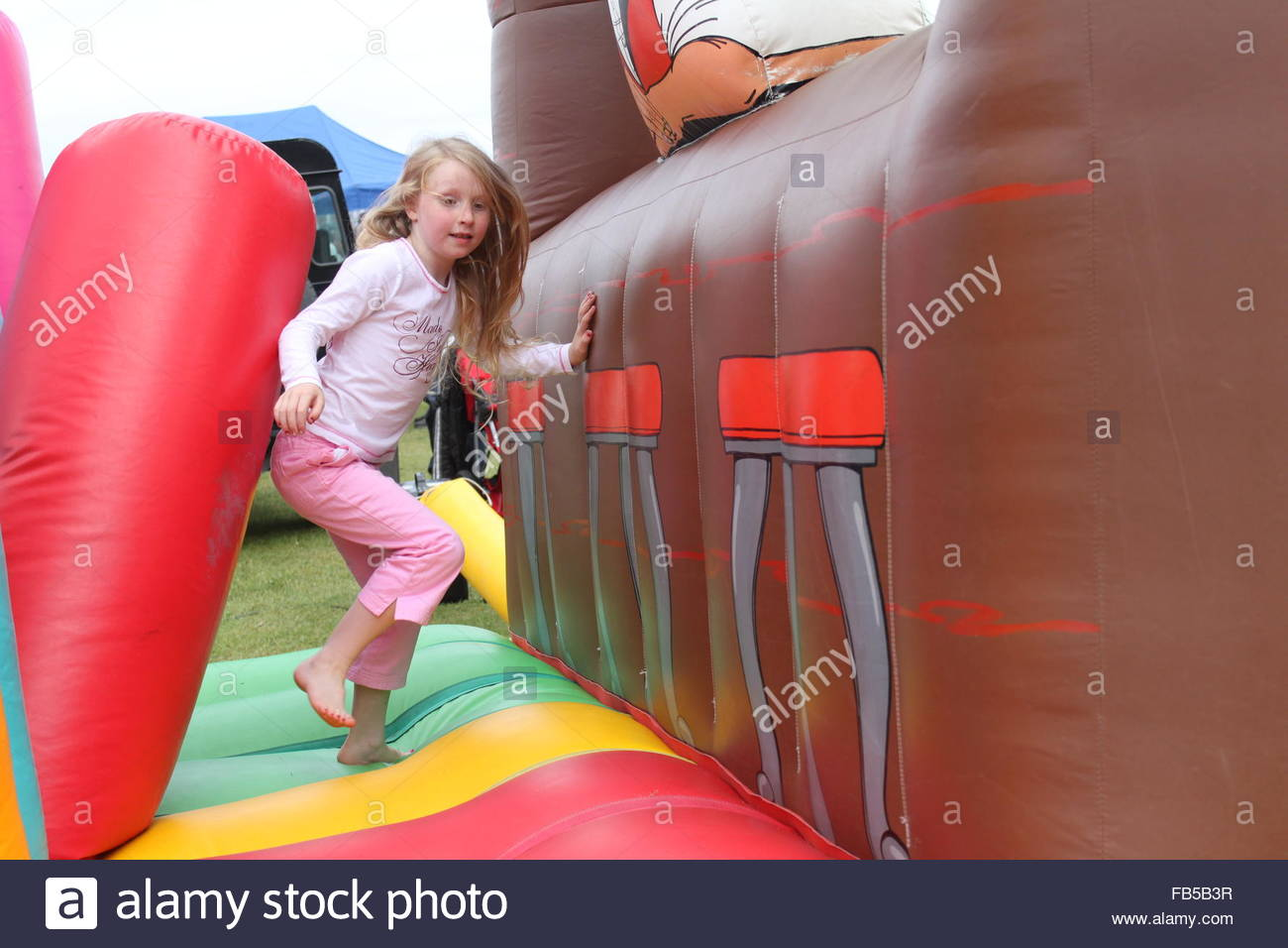 Young, cute blonde girl on a bouncy castle wearing pink summer clothes - Stock Image