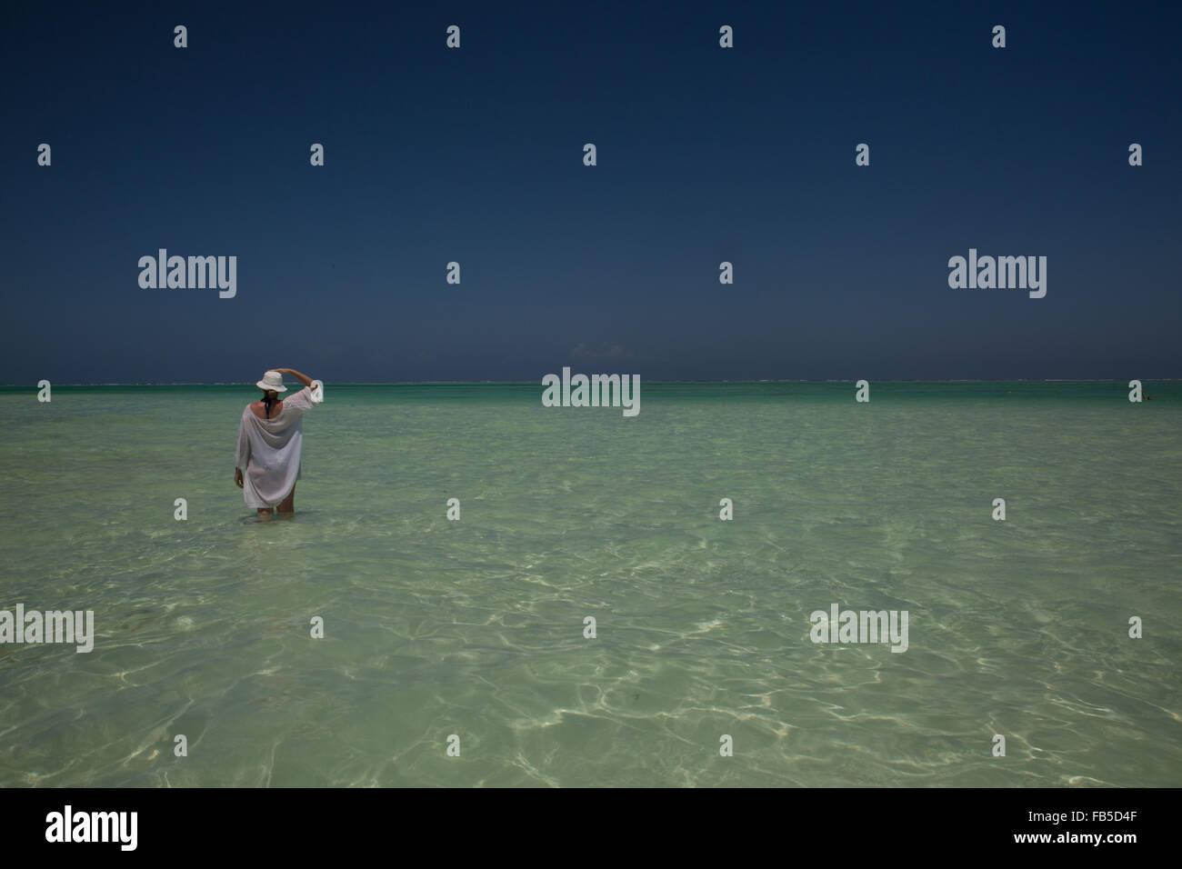 A lone figure in the sea on the beach Michamwi Michamwi Pingwe peninsula Zanzibar Tanzania - Stock Image