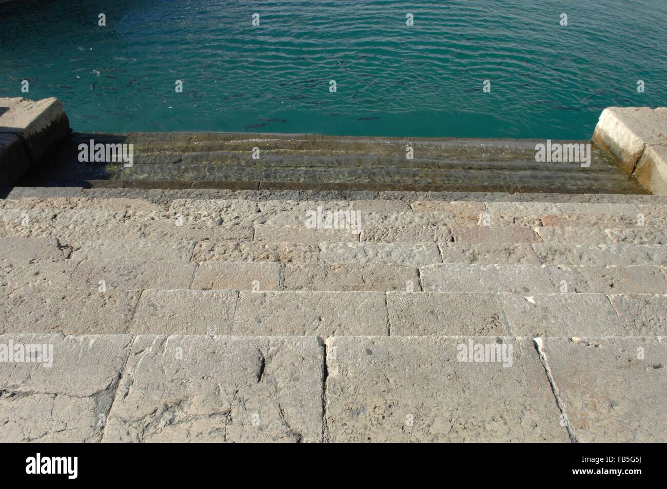 steps going down into the marina water for easy access to boats - Stock Image