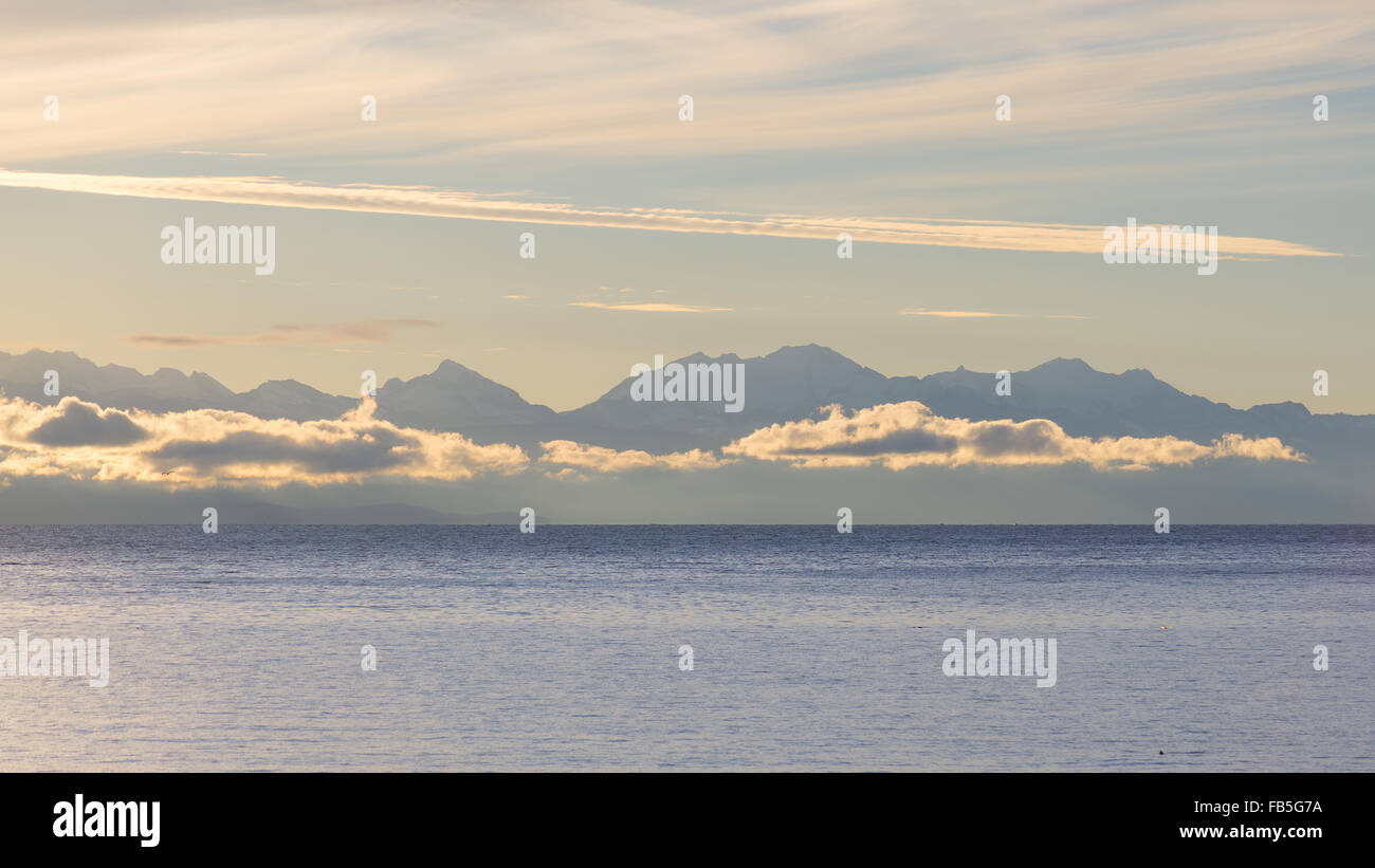 The majestic silhouette of the Cordillera Real mountain range at the horizon of the Titicaca Lake. Telephoto view - Stock Image