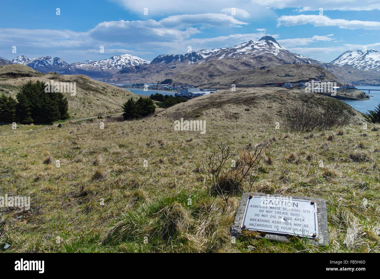 Alaskan landscape with sign reading 'Caution: Asbestos waste disposal site'. Dutch Harbor, Unalaska, AK, - Stock Image