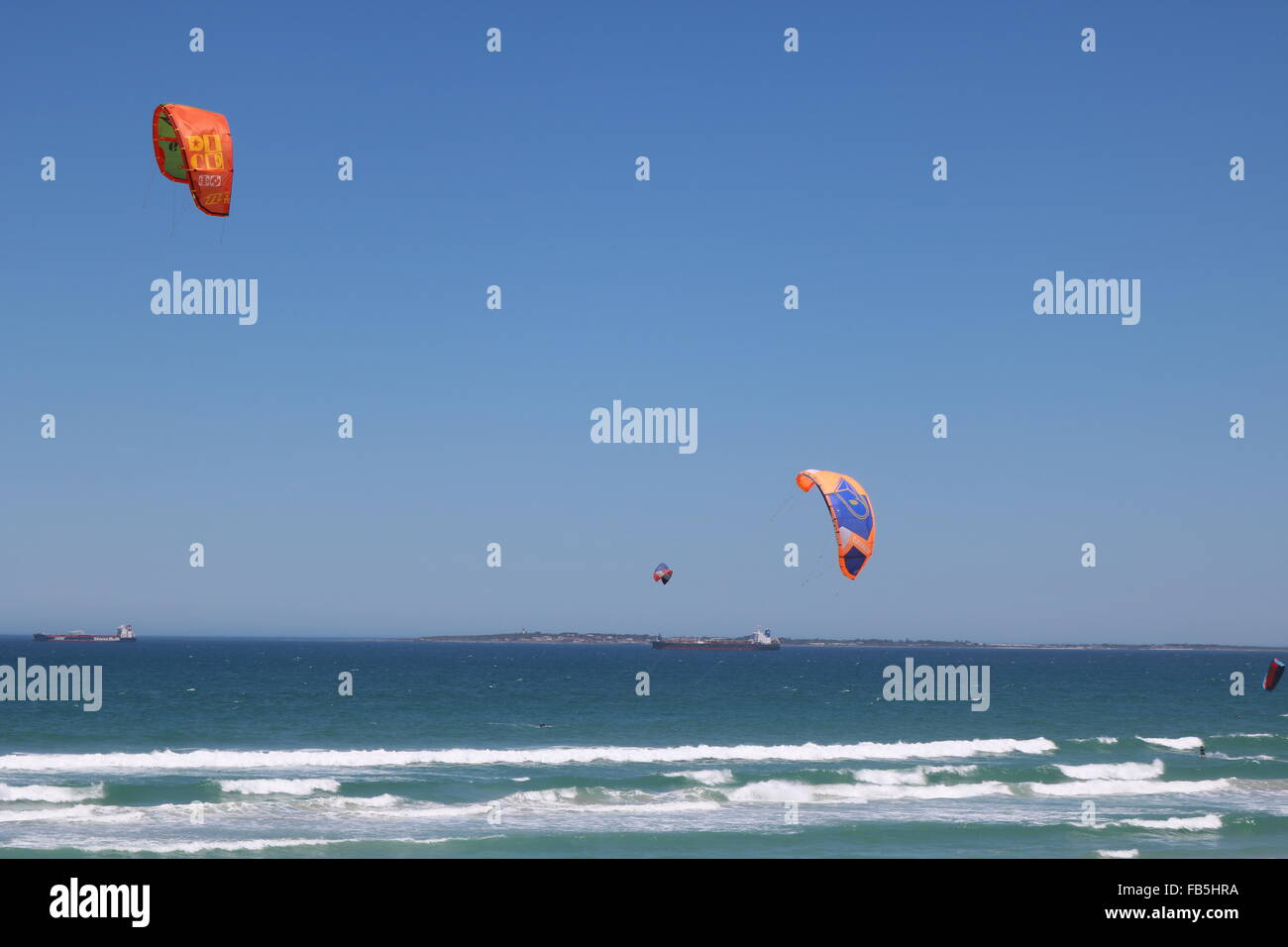 Kitesurfers at Bloubergstrand, Cape Town with Robben Island in the background - Stock Image