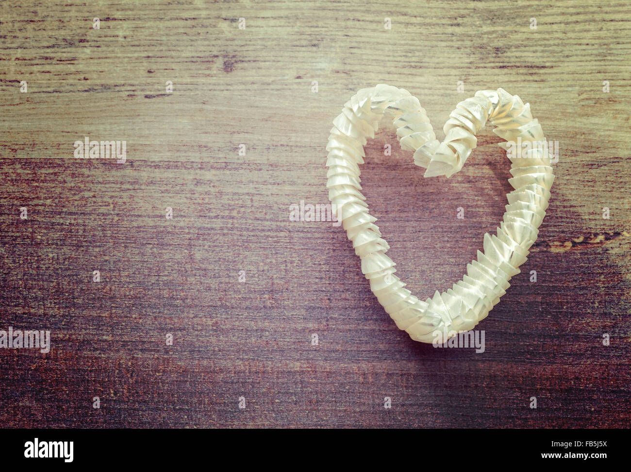 Vintage stylized heart made of shells on wooden background, space for text. - Stock Image
