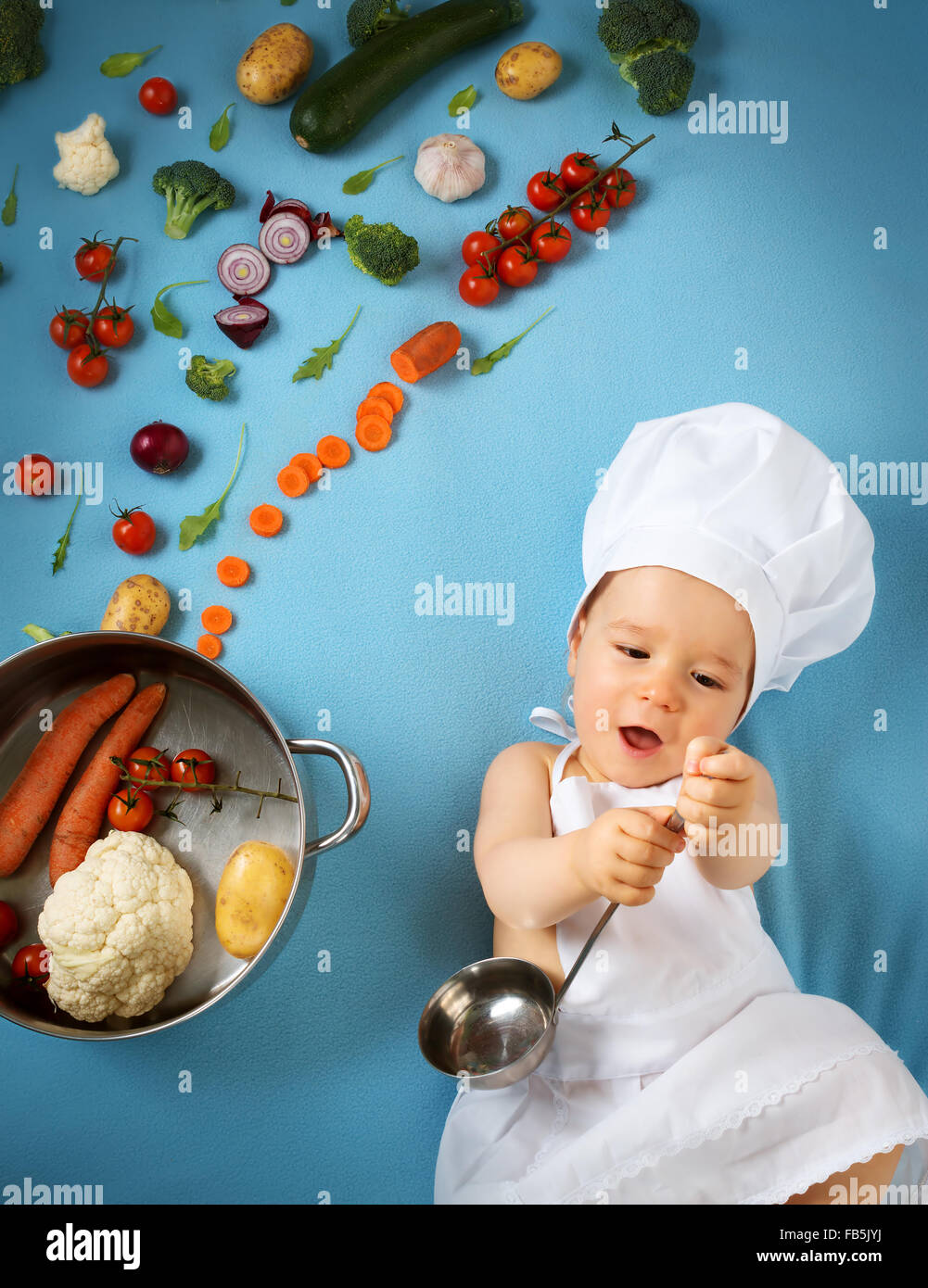 Baby boy in chef hat with cooking pan and vegetables - Stock Image