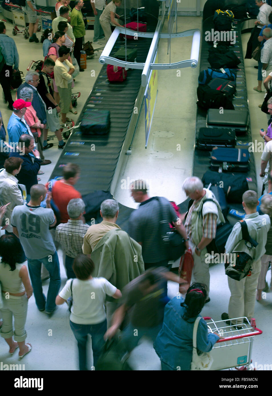 People at the airport waiting for their luggage at the Baggage conveyor belt - Stock Image