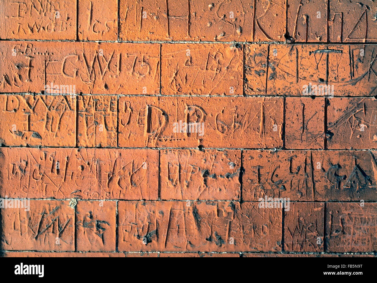 Brick Wall with carved signs and words - Stock Image