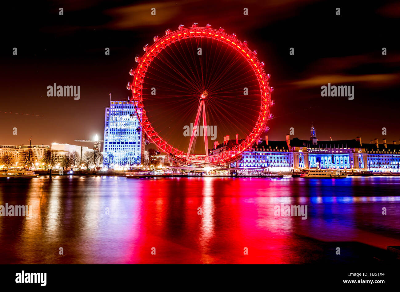 London Eye and nearby buildings on a winter evening, showing reflection in the River Thames - Stock Image
