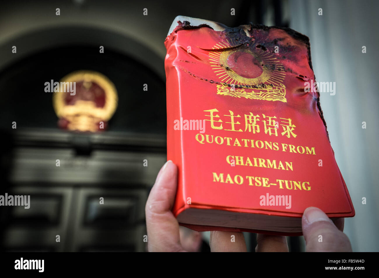 London, UK. 10th January, 2016. A protester holds up a partly burnt copy of 'Quotations from Chairman Mao Tse-tung' Stock Photo