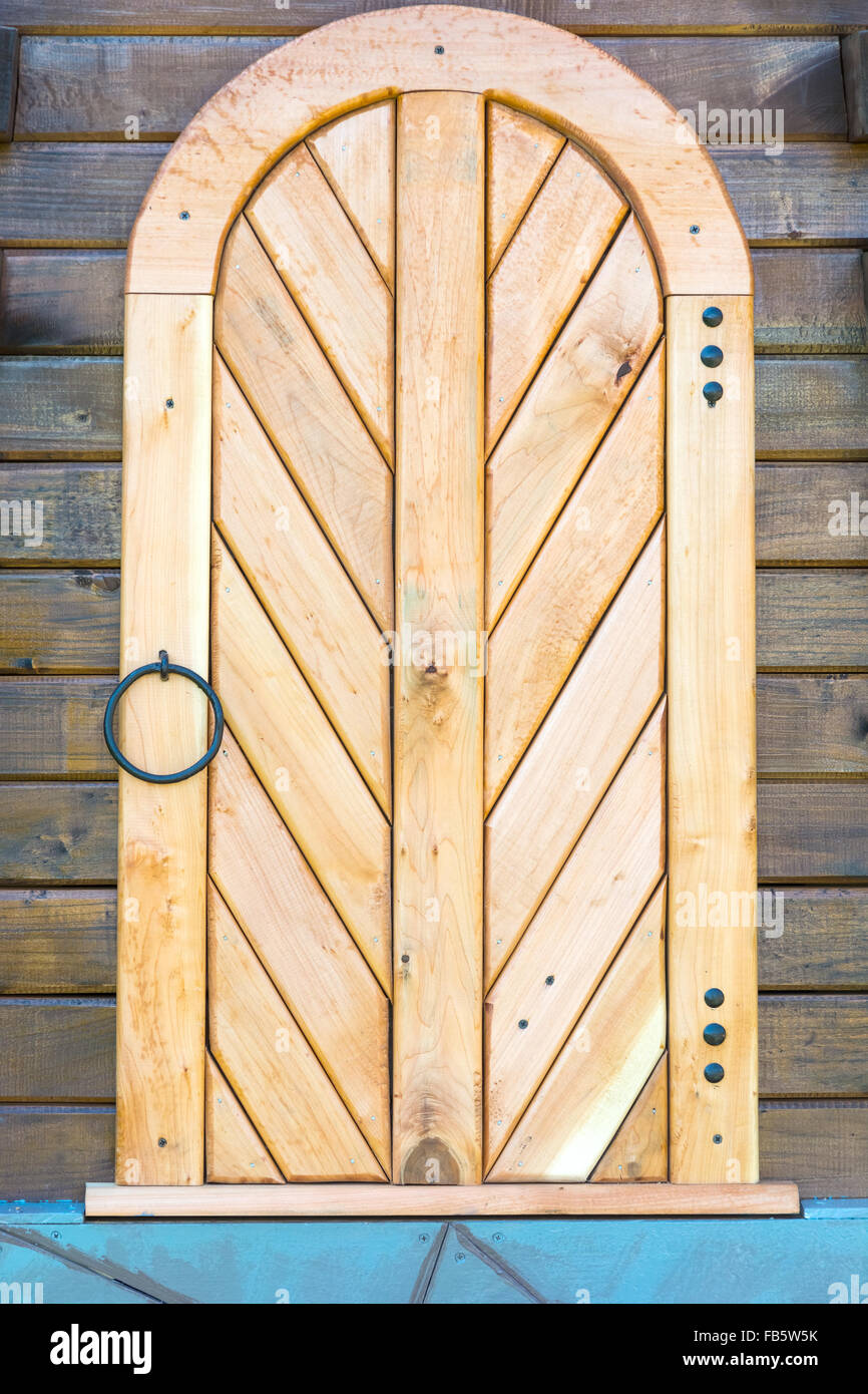 Old wooden door in the wall made of wooden logs. Decoration Stock ...