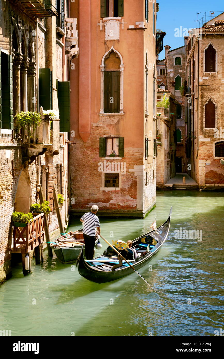 Gondolier flowing gondola, Venice canal, Veneto, Italy, UNESCO - Stock Image