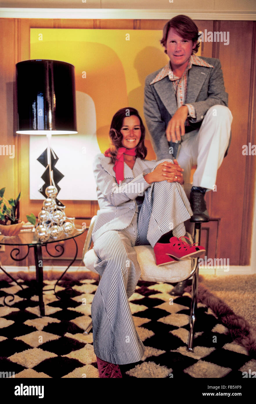 A young California couple pose for an indoor portrait in clothing and with home furnishings fashionable in the early - Stock Image
