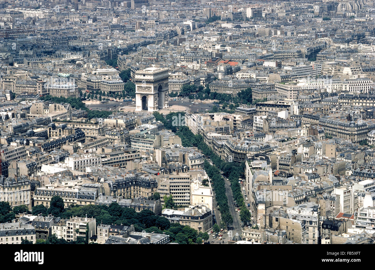 An aerial photograph shows the towering Arc de Triomphe standing out amid the many buildings and tree-lined boulevards - Stock Image