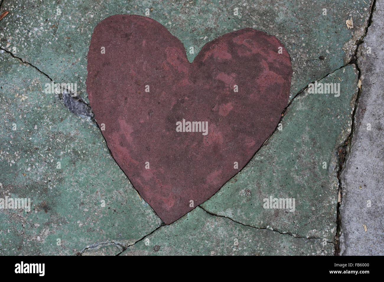 A heart shape in a cracked sidewalk. - Stock Image