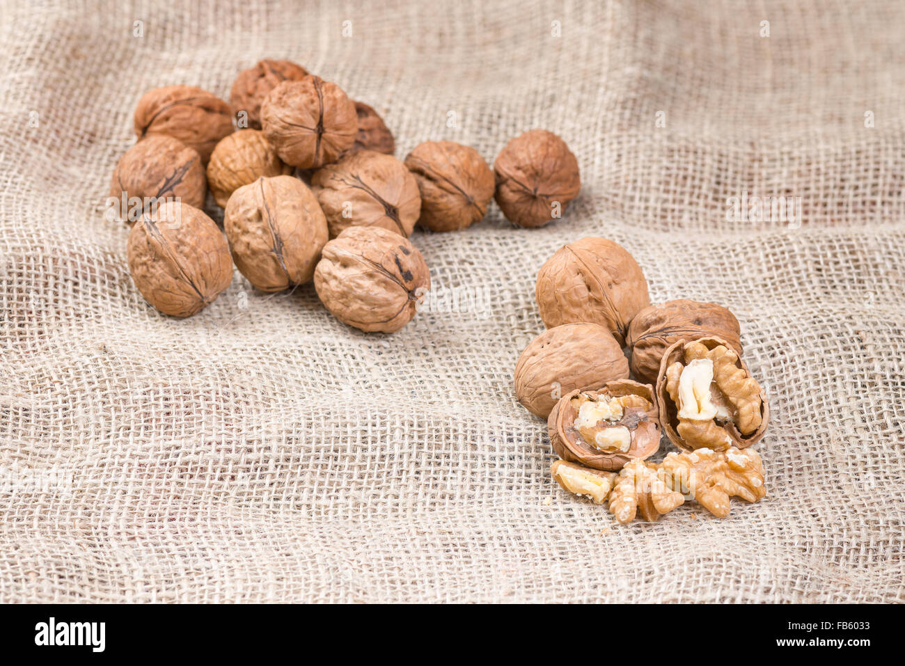 Walnut kernels and whole walnuts on rustic sack. - Stock Image