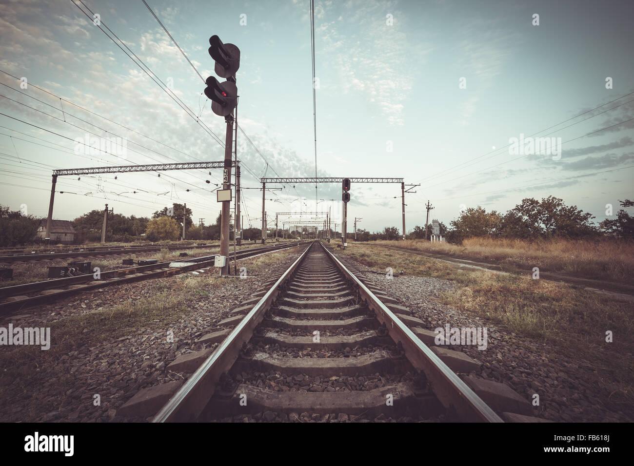 Train platform and traffic light at sunset. Railroad. Railway station. - Stock Image