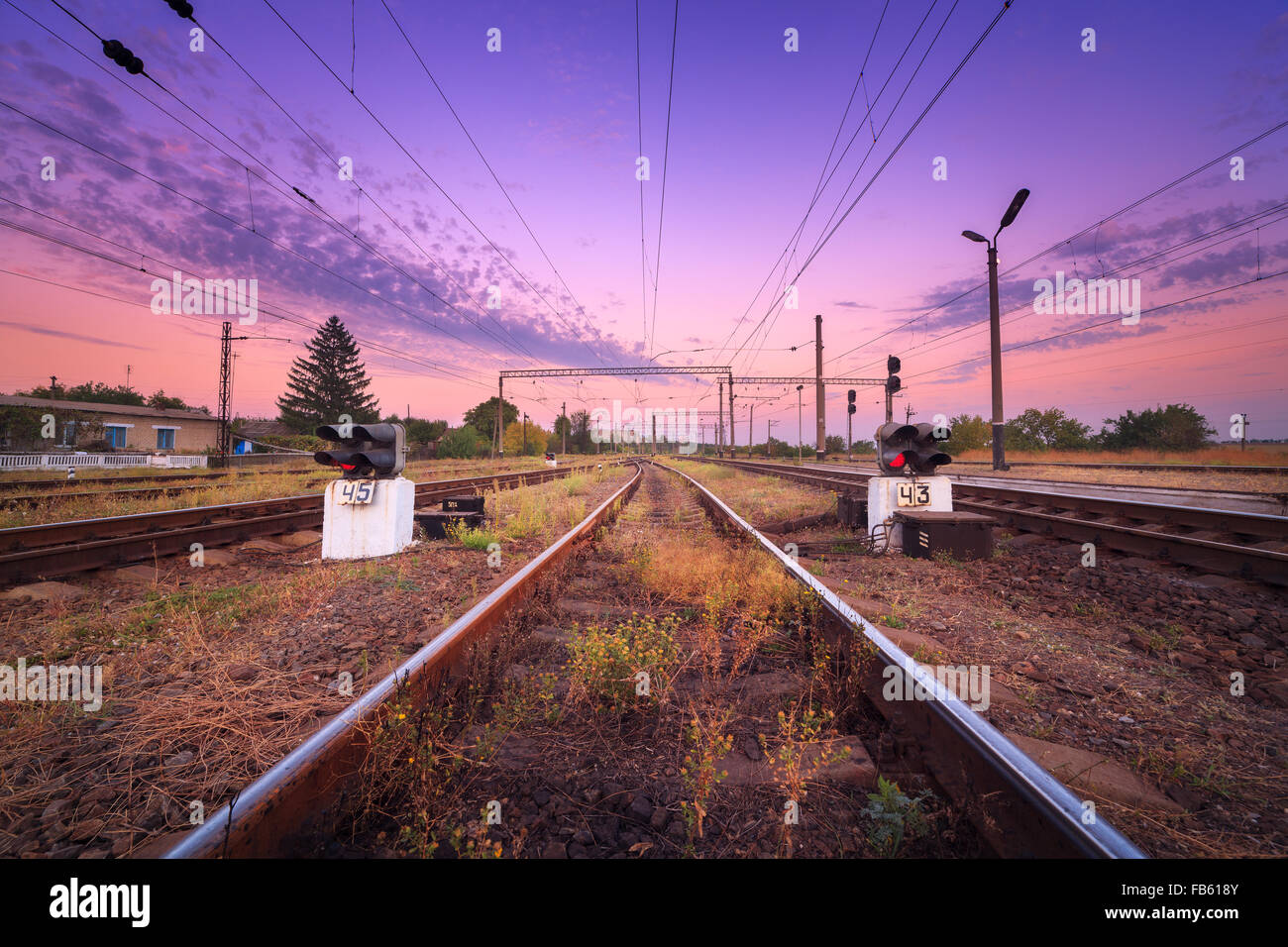 Train platform and traffic light at sunset. Railroad. Railway station - Stock Image