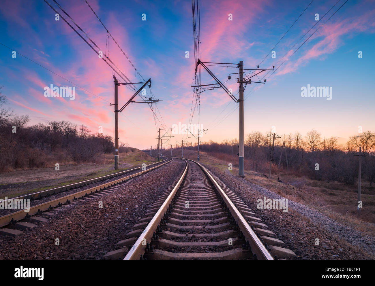 Train platform at sunset. Railroad in Ukraine. Railway landscape. - Stock Image