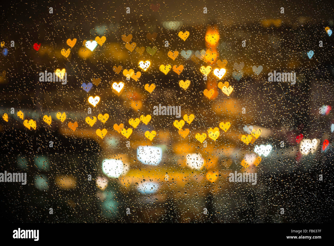 Small colorful hearth bokeh behind the wet glass for valentine day love concept background - Stock Image