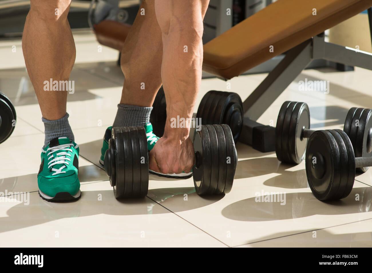 Bodybuilder picks up dumbbells. - Stock Image