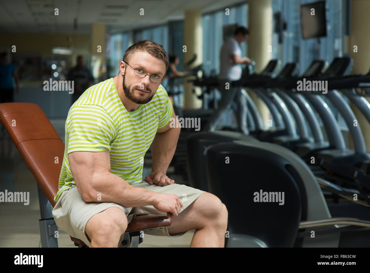 Bearded sportsman in gym. - Stock Image