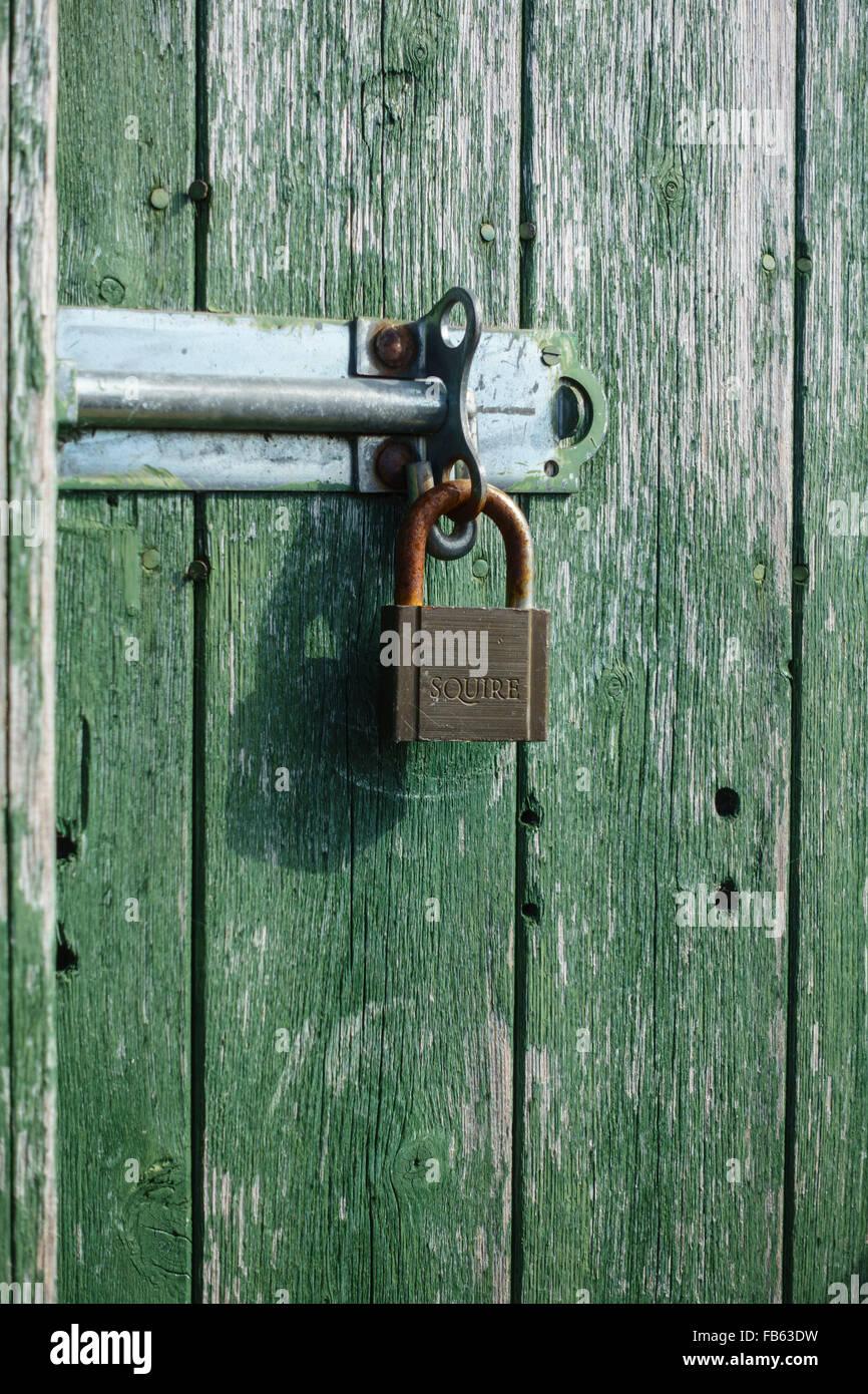 Padlock securing a closed door - Stock Image
