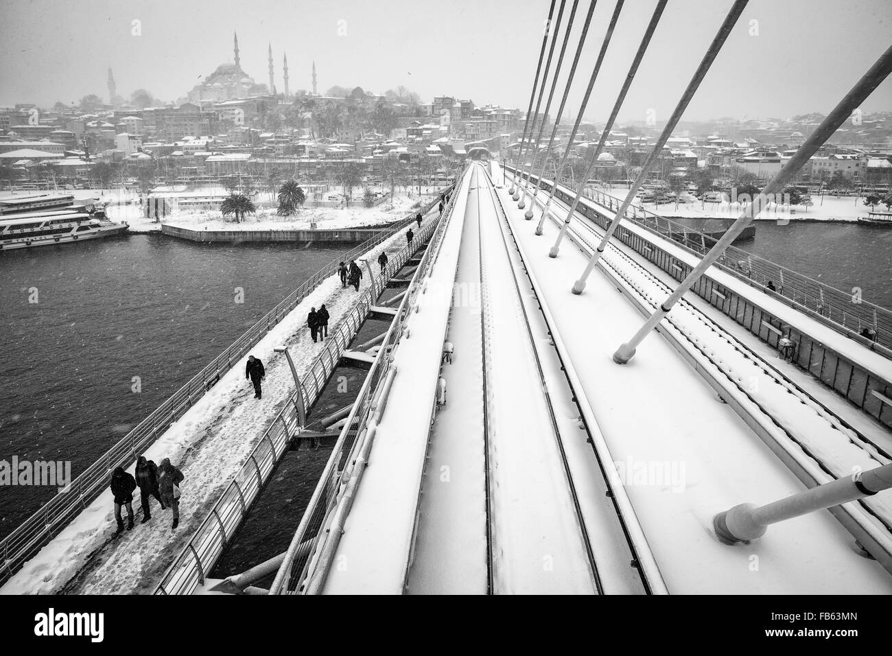 People walking on the Golden Horn Metro Bridge on a snowy day, 2016. - Stock Image