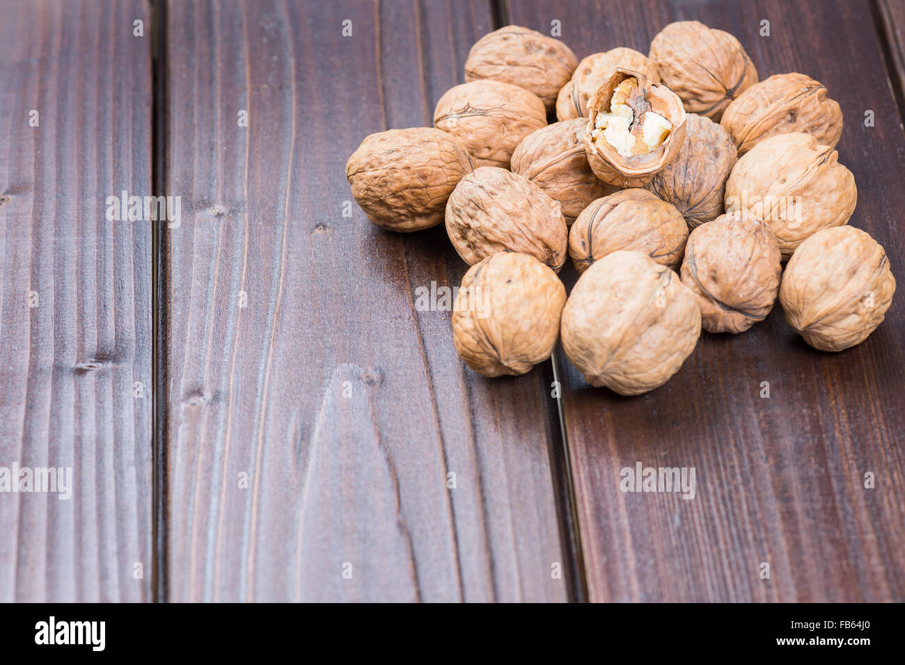 Walnut kernels and whole walnuts on rustic old wooden table - Stock Image