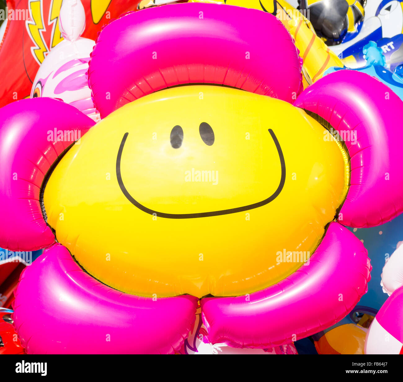 The sun in the face. Image of a flower smiley baloon that look and follow the sun - Stock Image