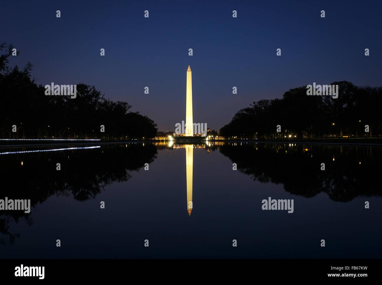 Washington Monument illuminated at night with reflection - Stock Image