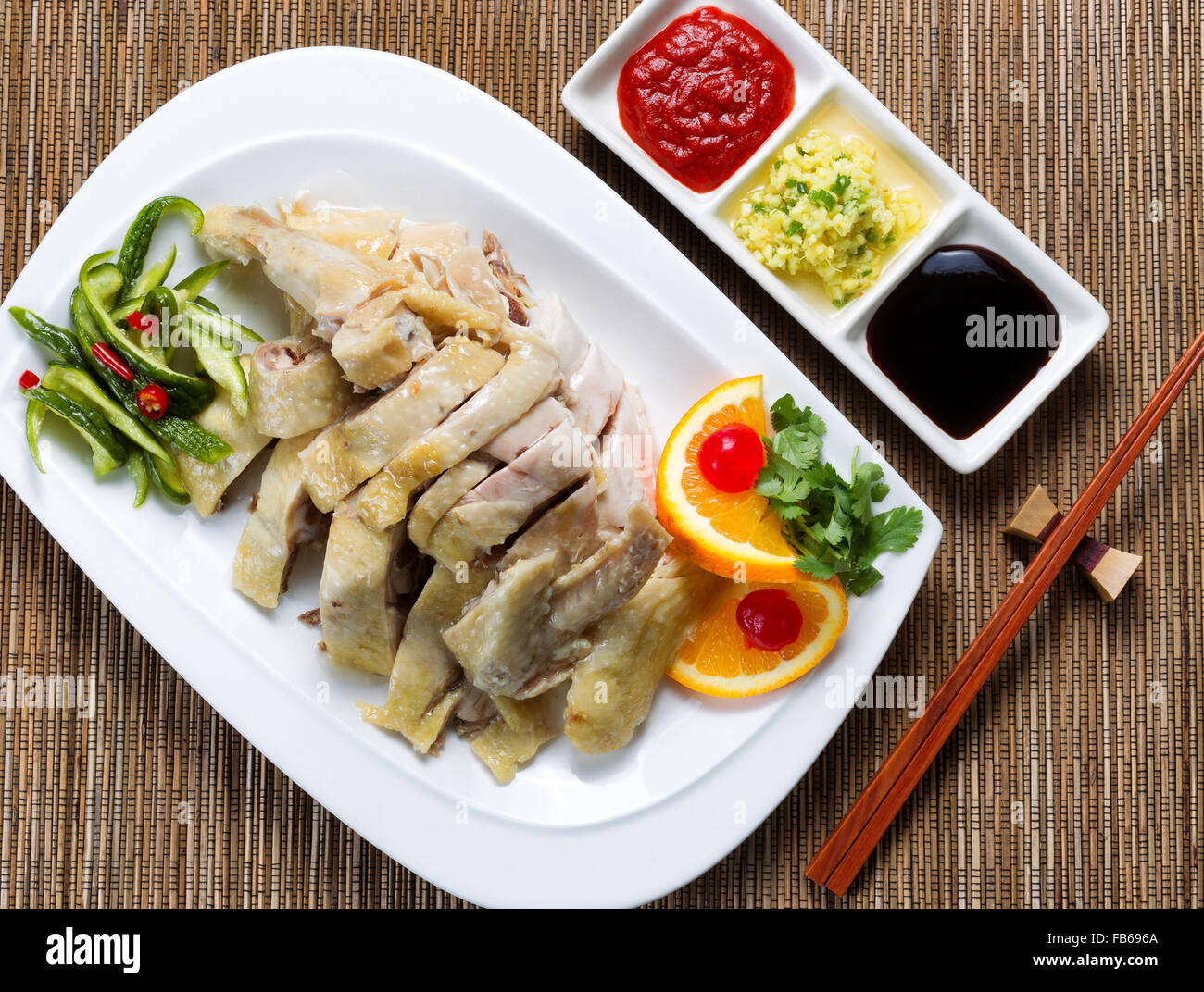 Top view of sliced roasted chicken and vegetables with dipping sauces. Bamboo mat underneath dish. - Stock Image