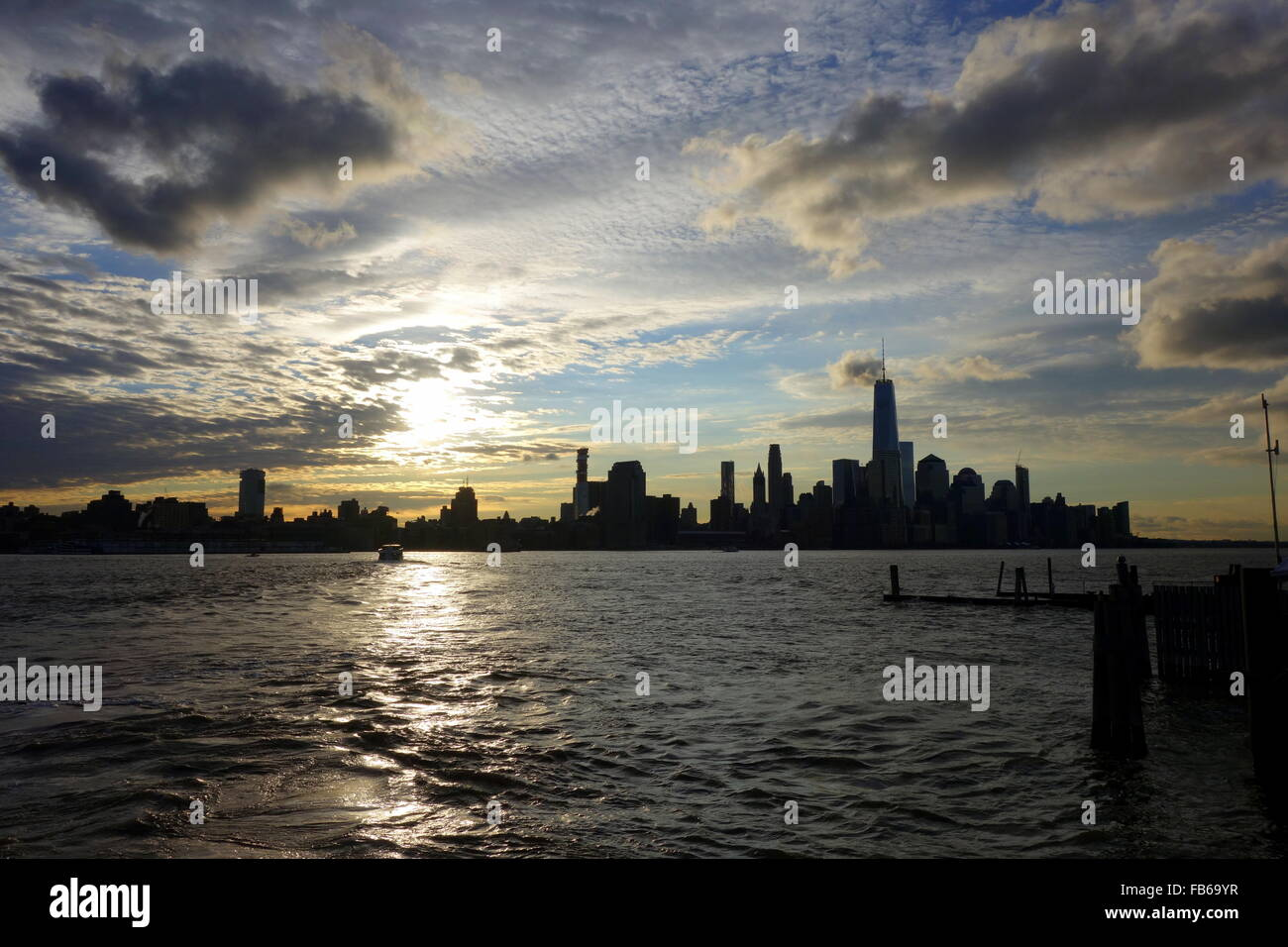 Moving clouds and gleaming sun framing silhouettes of the New York ...