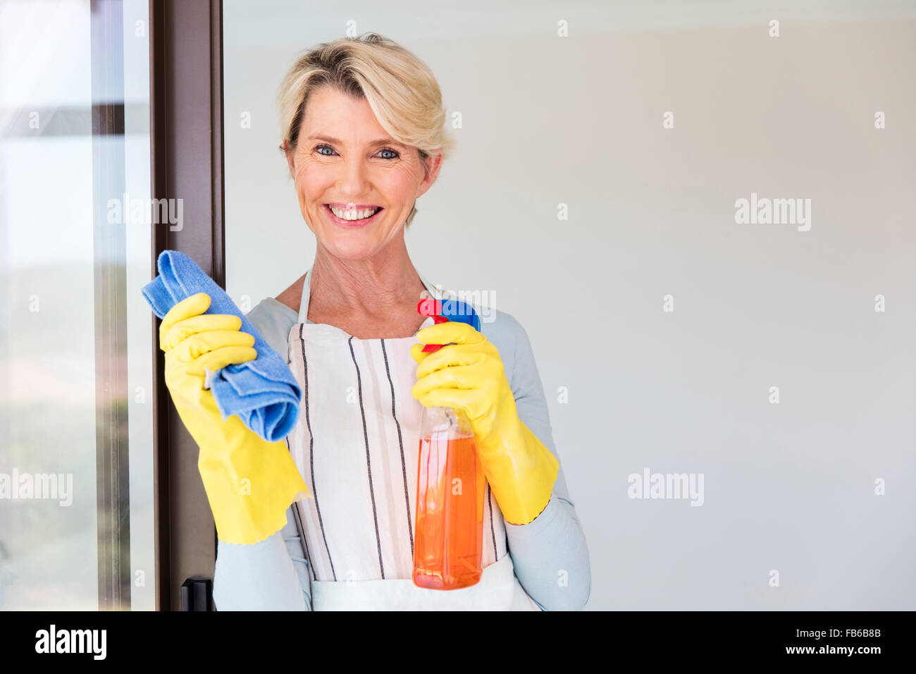beautiful senior woman cleaning her house Stock Photo