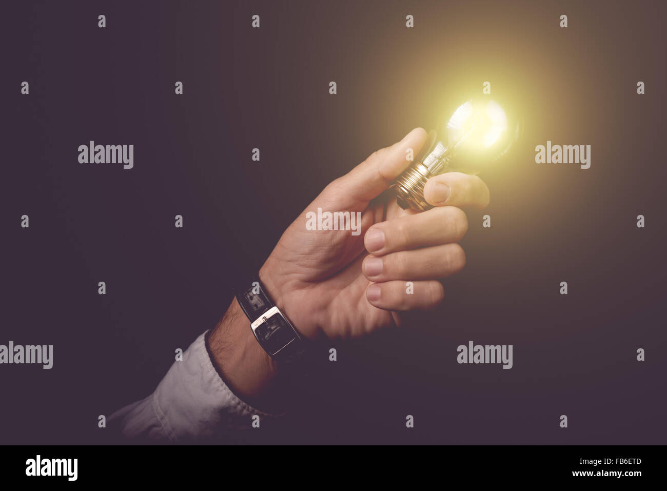 Businessman holding light bulb, concept of new ideas, business innovation and creativity, retro toned image, selective - Stock Image