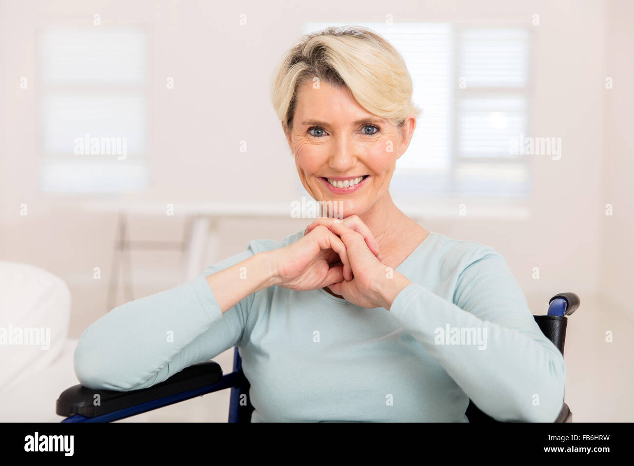 elegant senior woman sitting on wheelchair recovering from injury - Stock Image