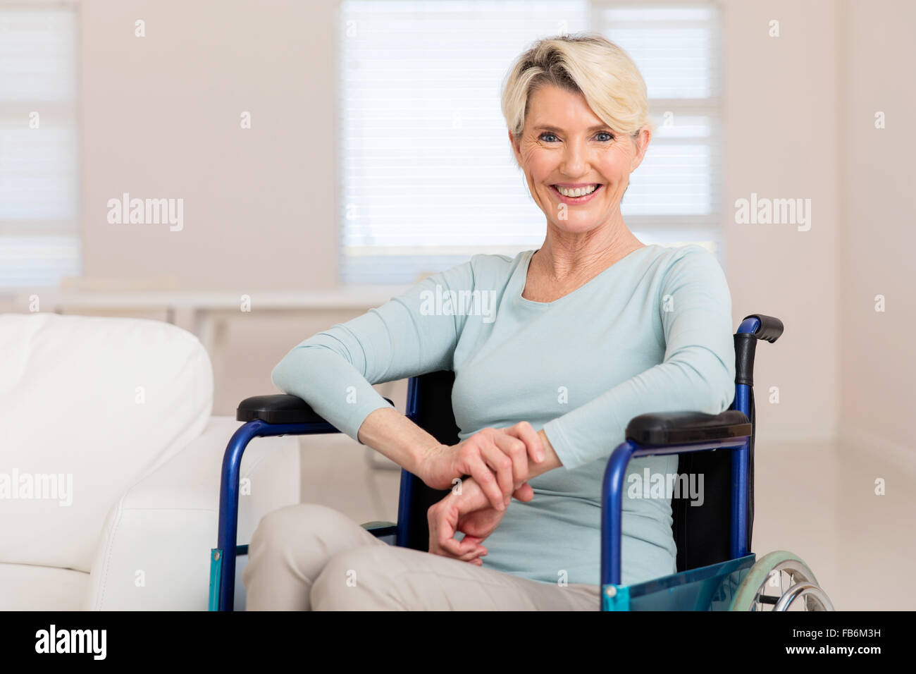 happy mid age woman sitting on wheelchair and recovering from sickness - Stock Image